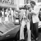Pat Riley shaking the hand of a smiling Magic Johnson after the Laker star was awarded this car and a trophy for winning MVP of the 1982 NBA finals.  Johnson averaged 16.2 points, 10.8 rebounds and 8.0 assists in that series against the 76ers.