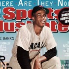 "July 7-14 |  When you think of the Chicago Cubs, the first name that usually comes to mind is Ernie Banks. Banks, along with former Dallas Cowboys offensive lineman Nate Newton, are featured in SI's ""Where are they now?"" double issue.  In the issue, Banks explains why the Cubs haven't won a World Series since 1908. ""First of all, Wrigley Field. It's a different place to play,"" Banks tells SI's Rich Cohen. ""I mean, the wind blows all kinds of ways. Foul lines are very close to the wall."""