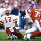Washington Redskins quarterback Doug Williams twists his leg late in the first quarter, forcing him the leave the game with the Denver Broncos up 10-0. Williams returned to throw for 340 yards and four touchdowns as the Redskins easily defeated the Broncos 42-10. Williams was the first black quarterback to play in the Super Bowl.