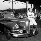 """Boston Braves outfielder Tommy Holmes waving his cap from the hood of this car awarded to him in 1945.  The vehicle was given on """"Tommy Holmes Day,"""" in which the team and its fans celebrated the Major League's leading hitter."""