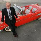 Former NBA player Kent Benson standing by his flashy red convertible in 2006.