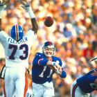 New York Giants quarterback Phil Simms tosses a pass around the outstretched arms of Denver Broncos linebacker Simon Fletcher. Simms carved up the Broncos defense for 268 yards and three touchdowns on 22-of-25 passing as the Giants dominated Denver 39-20.