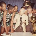 Boston Celtics owner Red Auerbach celebrates with the trophy and his team after beating the Houston Rockets in six games behind Finals MVP Cedric Maxwell and star Larry Bird.