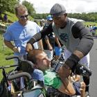 Cam Newton gives his shoes to fan Brian Cooper.