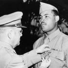 In the middle of his 140-month reign as World Heavyweight Champion, Louis voluntarily enlisted in the Army. Although Louis was originally assigned to a cavalry unit, the Army eventually placed him in the Special Services Division -- ensuring he would not see combat action -- in an effort to raise troop morale. Louis went on a celebrity tour along with fellow boxer Sugar Ray Robinson and staged boxing exhibitions around the world for his fellow soldiers. Louis was awarded the rare Legion of Merit in 1945, which qualified him for immediate release from the military.