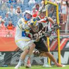 Denver Outlaws' Charlie Cipriano (right) hits and knocks the ball away from Kevin Cunningham of the Florida Launch during a Major League Lacrosse game at Sports Authority Field at Mile High in Denver, Colo.