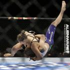 Ronda Rousey takes down Alexis Davis during their women's mixed martial arts bantamweight title bout at UFC 175 in Las Vegas.