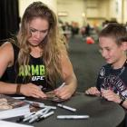Ronda Rousey signs an autograph during the UFC Fan Expo Las Vegas 2013 at the Mandalay Bay Convention Center in Las Vegas,.