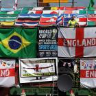 Employee Sean Mason hangs decorations and flags outside The Robin Hood public house in Jarrow, England, Monday, June 9, 2014 to create a display for World Cup 2014, which starts Thursday.