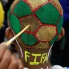 An Indian boy gets his head painted as part of a promotional event ahead of the soccer World Cup at a saloon in Mumbai, India, Monday, June 9, 2014. Soccer fans around the world are gearing up to watch the upcoming World Cup soccer tournament in Brazil.