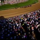 The field, led by California Chrome with jockey Victor Espinoza in tow, races into turn one at the Kentucky Derby.