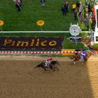 California Chrome passes Ride On Curlin, ridden by Joel Rosario, to win the Preakness.
