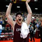 Peter Jasaitis raises the trophy in celebration after diminutive Loyola of Chicago defeated volleyball powerhouse Stanford to win its first Men's Volleyball Championship.