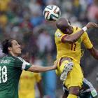 Cameroon's Stephane Mbia (17) heads the ball past Mexico's Andres Guardado during the first half of the group A World Cup soccer match between Mexico and Cameroon.