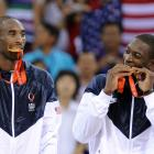 Kobe Bryant and Dwyane Wade test the authenticity of their medals after defeating Spain 118-107 to claim top prize.