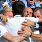 Novak Djokovic hugs his coach Boris Becker (left) and the rest of his team