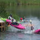Kayakers slide off a ramp for an exciting start the boater-cross races.