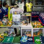 A shop attendant works amongst Japan World Cup team merchandise and FIFA World Cup 2014 merchandise at a football store on June 11 in Tokyo.