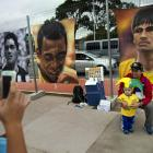A man poses for the picture with his son next to portraits of Brazilian soccer idols Neymar, right, Pele, center, and Garrincha, left, outside Arena Corinthians stadium in Sao Paulo on June 11.