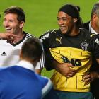 A fan bearing the resemblance of Ronaldinho is escorted off the field while talking to Lionel Messi of Argentina after an open training session on June 11 in Belo Horizonte, Brazil.
