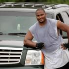 The Seahawks left tackle poses with his Cadillac Escalade, which he would push while exercising during the 2005 offseason.