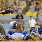 Los Angeles Dodgers' Yasiel Puig, right, and Chicago Cubs catcher Wellington Castillo, center, look to home plate umpire Jim Wolf for the call after Puig scored on a fielders' choice by Hanley Ramirez during the sixth inning of a baseball game on August 1, 2014 in Los Angeles, California.