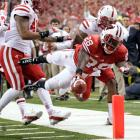 Wisconsin RB Montee Ball dives across a pylon to score one of his three touchdowns against Nebraska in the Big Ten Championship. The Badgers routed the favored Cornhuskers 70-31.