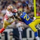 49ers tight end Delanie Walker and Rams safety Quintin Mikell battle for a pass.