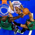 Kevin Garnett (left) and Paul Pierce surround Evan Turner as he goes up for a shot. The 76ers won 95-94 in overtime.
