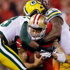 Green Bay Packers free safety M.D. Jennings and outside linebacker Erik Walden tackle San Francisco 49ers quarterback Colin Kaepernick in the second quarter of their playoff game. Kaepernick had a field day running the ball, setting a record for rushing yards by a quarterback in any game with 181 yards on the ground.