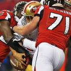 Colin Kaepernick tries to hang onto the ball while being tackled by Stephen Nicholas (54) and Kroy Biermann.