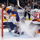 New York Islanders goaltender Evgeni Nabokov deflects the puck behind the net on a shot from the New Jersey Devils' Mattias Tedenby. The Devils got the win, 2-1, ruining the Islanders' home opener.