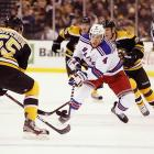 Rangers defenseman Michael Del Zotto chases the puck toward Bruins blueliner Johnny Boychuk, whose third-period goal helped put away the New York Rangers on opening day of the NHL season.