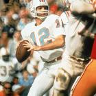 Miami Dolphins quarterback Bob Griese stands in the pocket and looks to pass against the Washington Redskins defense. Griese recovered from a fractured right leg and dislocated ankle suffered in the fifth week of the season to lead the Dolphins to a 14-7 victory, completing eight of 11 passes for a touchdown with one interception.