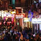 People walk along Bourbon Street in downtown New Orleans, as revelers gathered in the city's French Quarter.