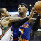 Milwaukee's Monta Ellis puts an arm bar on New York's Carmelo Anthony as he goes up for a shot.