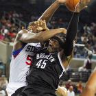 Brooklyn's Gerald Wallace's flight to the basket is halted by Philadelphia's Kwame Brown.