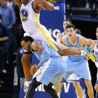 Andre Iguodala of the Denver Nuggets is fouled by a leaping Jarrett Jack of Golden State.