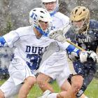 Notre Dame's Matt Miller checks Duke's Jordan Wolf during a snowy battle between the two lacrosse teams in Durham, N.C. The Fighting Irish scored the first six goals of the game to cruise to a 13-5 season-opening victory.