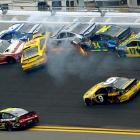 Trevor Bayne (21), Carl Edwards (99), David Gilliland (38), Terry Labonte (32), David Ragan (34) and Ricky Stenhouse Jr. (17) collide between Turn 1 and Turn 2 as Jeff Gordon (24) and Marcos Ambrose (9) drive by.