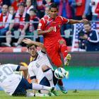 Carlos Rodriguez leaps over U.S. defenders Geoff Cameron (20) and Brad Evans.