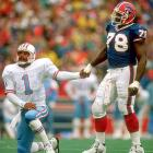 Oilers QB Warren Moon takes Smith's help after being knocked to the ground during a playoff game.
