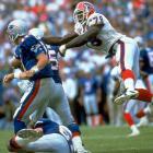Smith leaps past blockers in pursuit of Patriots QB Drew Bledsoe.