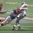 Cowboys RB Emmitt Smith attempts to turn away as Bruce Smith dives to make the tackle.