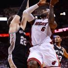 The Heat's LeBron James (6) attempts to drive past the Spurs' Tiago Splitter.