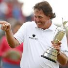 Phil Mickelson smiles as he holds the Claret Jug trophy.