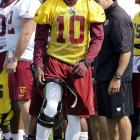 Washington Redskins quarterback Robert Griffin III adjusts his knee brace during training camp at the team's new practice facility in Richmond, Va.