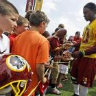 Griffin III signs autographs for fans after a Redskins practice.