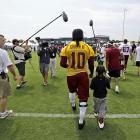 Griffin III walks off the field with fan Michael Dabney, 7, of Richmond.