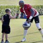 Carolina Panthers quarterback Cam Newton gives a fist-bump to Max Kalinowski, 6, of Spartanburg, S.C., during camp in Spartanburg.